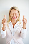 Excited young female showing thumbs up sign