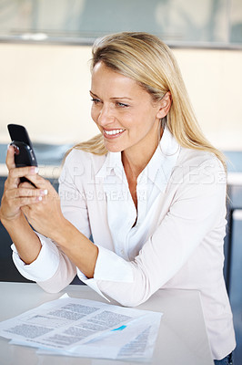 Buy stock photo Portrait of a happy young businesswoman typing a text sms message in her cellphone at office