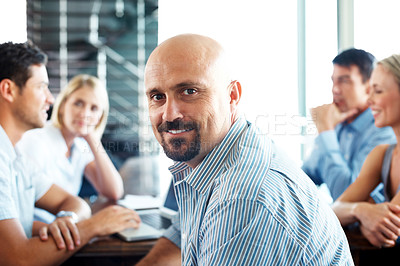 Buy stock photo Portrait of a handsome businessman glancing back in a meeting with his business colleagues