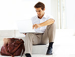 Young businessman sitting on steps using laptop