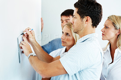 Buy stock photo Handsome young businessman drawing a chart on a whiteboard with his business colleagues