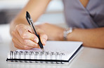 Woman's hand holding a pen taking notes