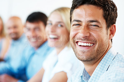 Buy stock photo Closeup of a handsome young businessman smiling in a meeting with his colleagues in background