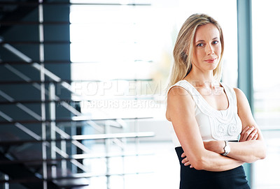 Buy stock photo Portrait of a smiling young casual businesswoman standing with her hands folded