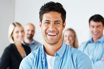 Buy stock photo Portrait of a confident young business man smiling with people in background