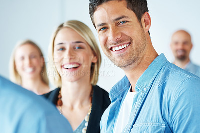 Buy stock photo Portrait of a happy man and woman smiling together with colleagues around