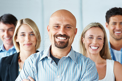 Buy stock photo Portrait of a mature businessman standing confidently with his group at office