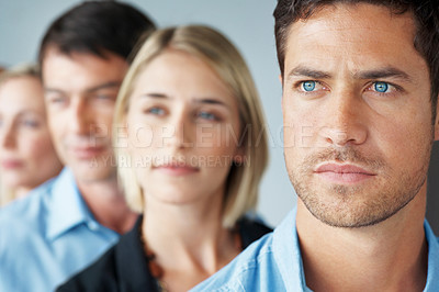 Buy stock photo Portrait of a confident young businessman looking away with his team in background