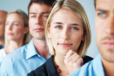 Buy stock photo Portrait of a smart young businesswoman standing in row with colleagues