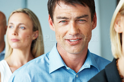 Buy stock photo Portrait of a happy young businessman standing in a row with colleague at office