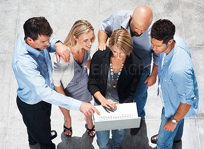 Buy stock photo Top view of group of business executives discussing work on laptop