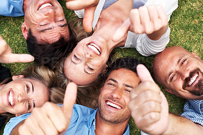 Buy stock photo Portrait of a group of smiling people lying together on grass giving the camera above them thumbs up