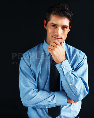 Buy stock photo Young business man holding hand up to chin with arms folded