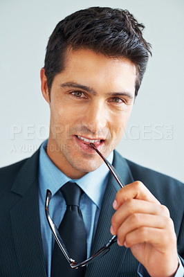 Buy stock photo Young executive holding eyeglasses up to mouth while looking directly at you