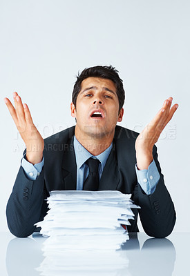 Buy stock photo Executive looking hopeless while sitting behind stack of papers