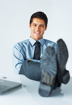 Buy stock photo View of successful executive resting his feet on desk