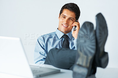 Buy stock photo Businessman on phone resting with feet on desk in front of laptop
