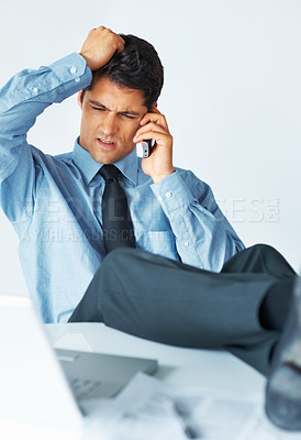Buy stock photo Businessman with feet on desk looking confused while on phone