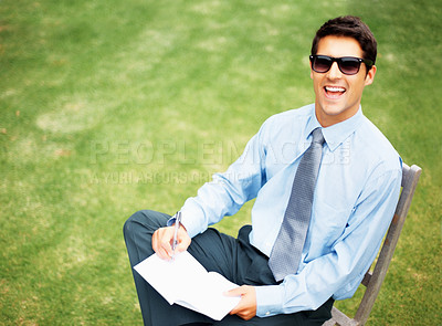 Buy stock photo Happy young male executive sitting outside in a park in his lunch break - copyspace