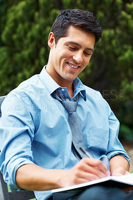Buy stock photo Businessman sitting outdoors and writing