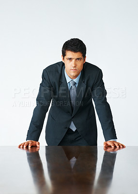 Buy stock photo Executive standing and leaning with hands on table