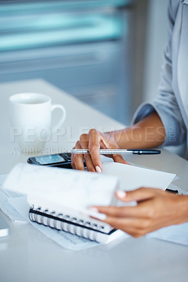 Buy stock photo View of woman's hands flipping through pages of a notebook at her desk with cellphone and a mug of coffee next to her