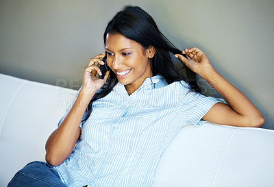 Buy stock photo Attractive woman having phone conversation while on sofa