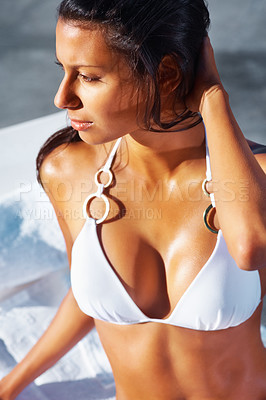 Buy stock photo Beautiful woman with a stunningly tanned skin wearing a bikini and sitting up looking into the distance