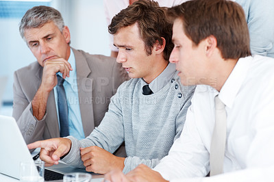 Buy stock photo Young businessman discussing work with his colleagues while working on laptop