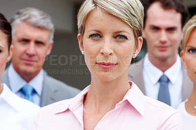 Buy stock photo Attractive young female business executive looking confidently with her coworkers in background