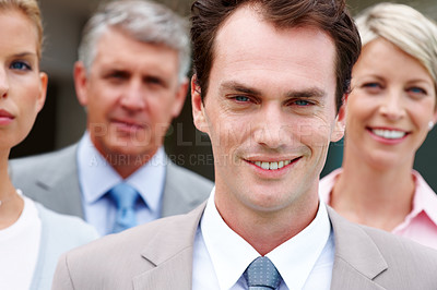 Buy stock photo Confident young business man smiling with his colleagues in background