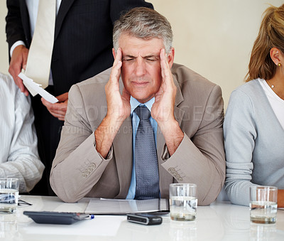 Buy stock photo Portrait of a elderly businessman having headache at meeting while sitting with other colleagues
