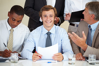 Buy stock photo Happy young businessman sitting with his colleagues at a meeting in office