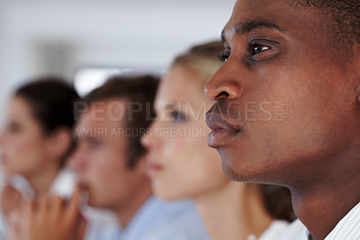 Buy stock photo Young afroamerican male executive paying attention to a seminar with coworkers in background