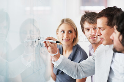 Buy stock photo Business people looking at their leader while he explaining something on whiteboard