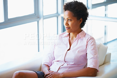 Buy stock photo Beautiful young business woman sitting on couch and looking away