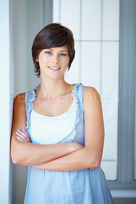 Buy stock photo Confident young business woman with hands folded leaning against wall