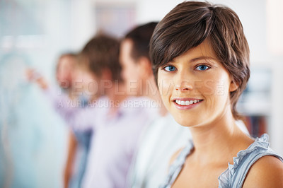 Buy stock photo Closeup of pretty young woman smiling at you with work colleagues in the background - copyspace