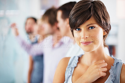 Buy stock photo Focus on happy young woman with team in blur background