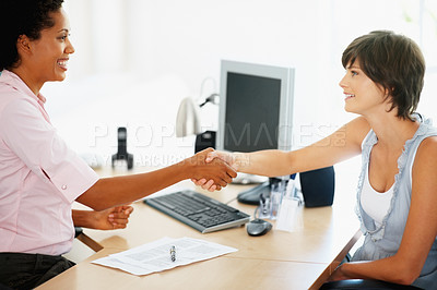 Buy stock photo Pretty young woman shaking hands with their insurance advisor