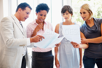 Buy stock photo Leader discussing reports with his team