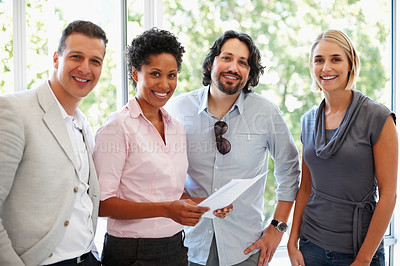 Buy stock photo Smiling young business woman holding document with her team