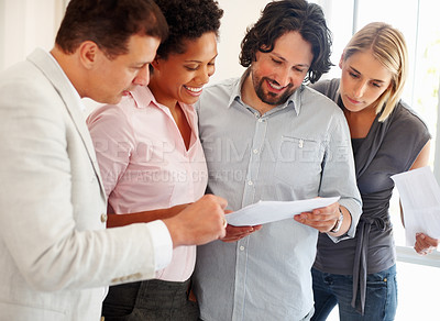 Buy stock photo Team of young business people reading the document
