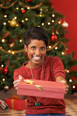 Buy stock photo Shot of an attractive young woman holding out her Christmas gift