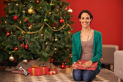 Buy stock photo Portrait of an attractive young woman sitting with her present at the Christmas tree
