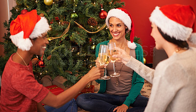 Buy stock photo Three happy young women toasting each other next to the Christmas tree