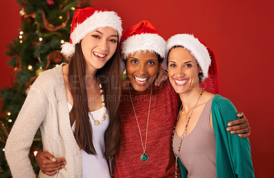 Buy stock photo Portrait of three happy young women wearing santa hats at Christmas