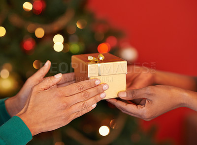 Buy stock photo Shot of two unrecognizable women exchanging gifts at Christmas