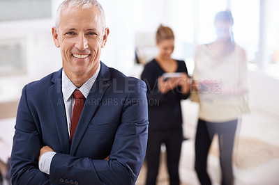 Buy stock photo Cropped shot of a mature businessman with two colleagues chatting in the background