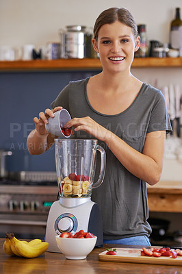 Buy stock photo Portrait of an attractive young woman adding fresh fruit to a blender to make a smoothie